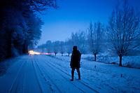 Lone walker in traditional snow scene in The Cotswolds, Swinbrook, Oxfordshire, United Kingdom