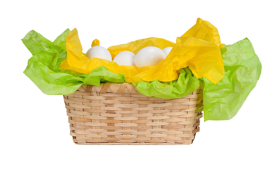 Basket with eggs and tissue paper yellow and green.