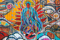 A colorful interpretation of the Virgin of Guadalupe painted by an unknown artist on a fence along a rural road in Taos, New Mexico, is reminiscent of the style of painter Wilem De Kooning
