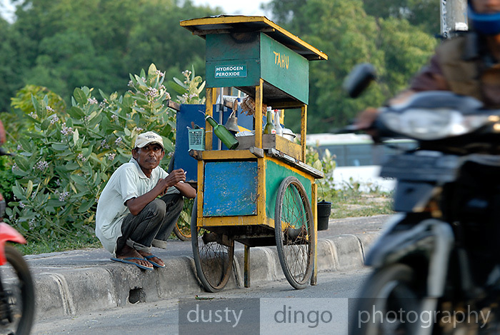 A Tahu vendor. Tahu is a soybean curd, also known as tofu. A sign on the cart indicates the vendor uses Hydrogen Peroxide to sterilise his implements. Jimbaran Bay, Bali, Indonesia.