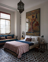 A guest bedroom is simply furnished with a window seat and a bed covered in local fabric