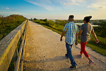 South Merrick, New York, USA - September 7, 2014 - A man and woman, seen from behind, walk during a late summer day with pleasant weather at Norman J Levy Park and Preserve marshland on Long Island, New York.