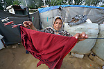 Fadia, who escaped fighting in Aleppo, Syria, hangs laundry to dry in front of her family's shelter in the Aamer al Sanad refugee settlement in Kab Elias, a town in Lebanon's Bekaa Valley which has filled with Syrian refugees. Two of her ten children were killed in Syria's civil war. <br /> <br /> Lebanon hosts some 1.5 million refugees from Syria, yet allows no large camps to be established. So refugees have moved into poor neighborhoods or established small informal settlements in border areas. International Orthodox Christian Charities, a member of the ACT Alliance, provides support for refugees in Kab Elias, including a community clinic.