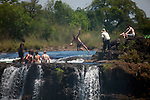 Africa, Zimbabwe, Victoria Falls. Tourists at Victoria Falls, cooling off in shallows at top of falls.