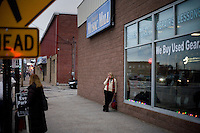 A woman stands outside the Mitt  Romney New Hampshire campaign headquarters in Manchester, New Hampshire, on Jan. 7, 2012. Romney is seeking the 2012 Republican presidential nomination.