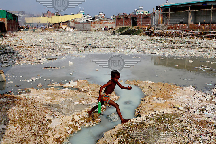 A small boy walks barefoot across a stream of water in the heavily polluted Buriganga River. Everyday 1.5 million cubic metres of waste water from 7,000 industrial units in surrounding areas and another 0.5 million cubic metres from other sources are released into the river. Although the government have enacted laws that require industry to safely process effluents these are rarely enforced and pollution remains uncontrolled. The river is biologically dead and increasingly a serious health hazard to those using and living near it.
