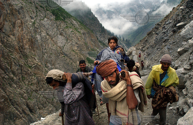 A Hindu woman and her child are carried by palanquin bearers (chairs carried on poles by two or four people) as they make their pilgrimage to the holy cave of Amarnath, one of the most revered Hindu shrines, near Baltal. 21,000 paramilitary soldiers and policemen were deployed along the mountain route to protect the pilgrims from Islamic guerrillas, who have been fighting for independence of the Indian-controlled portion of Kashmir since 1989.