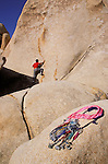 Rock climbing gear on granite rock (climber on rock wall in background), Hidden Valley, Joshua Tree National Park, California
