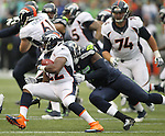 Seattle Seahawks defensive end Frank Clark (55) drags down Denver Broncos running back C.J. Anderson (22) behind the line of scrimmage for a loss during the first quarter at CenturyLink Field on August 14, 2015 in Seattle Washington.  The Broncos beat the Seahawks 22-20.  © 2015. Jim Bryant Photo. All Rights Reserved.
