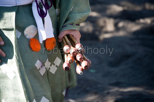 A young attendant carries back the arrows that found their target to return to the mounted archers during the Yabusame mounted archery ritual on the 3-day Reitaisai grand festival in Kamakura, Japan on  16 Sept. 2012.  In the Azumakagami -- a book of Japanese history covering 87 years from 1180 to 1266 in the Kamakura Era, a hunt and mounted archery event was held on August 15 1187 and it is this in which the shrine's Reitaisai has its roots. For over 800 years since the history and tradition of the event have been continued at the shrine. Photographer: Robert Gilhooly