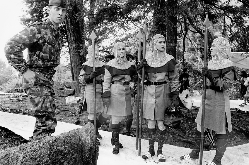 Switzerland. Canton Uri. Rütli feld. 1 August 1991. Swiss national holiday. Public holiday.  A soldier wearing a military outfitt stands close to a group of dancers, all women dressed as soldiers from the Middles Ages and holding spears in their hands. Rütli is the birthplace of the Swiss Confederation. © 1990 Didier Ruef