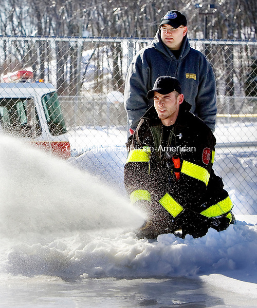 WOLCOTT, CT 16 January 2008-011609SV11--Firefighters Mike Couture Jr. and Jason Kordys spray water on the towns ice rink at Peterson Park in Wolcott Friday.<br /> Steven Valenti Republican-American
