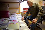 "Ron Grassi works on a legal brief in his Tahoe City, Calif. ""war room""/guest bedroom May 13, 2010. Grassi is suing the big three ratings agencies after he lost $40,000 on a Lehman Brothers bond."