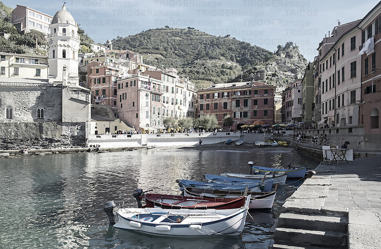 Boats are moored in Vernazza harbor with the town square in the background.