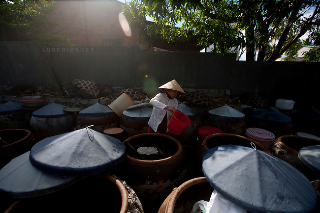 Tam makes fish sauce in the early morning light at Sau Phong, a low budget fish sauce factory in Mui Ne.