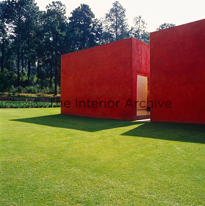 The red colour and angular shape of these large exterior walls juxtapose with the natural greens and organic shapes of the trees and garden