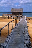 A raised walkway of bleached wooden planking extends out across the sand at low tide to a simple building made of local thatch