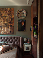 The walls of the guest bedroom are hung with a collection of paintings and decorative objects
