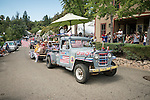 1950s Willy's Jeep pick up with flags pulling a float. Downtown main street during the Independence Day celebration Main Street, Mokelumne Hill, California