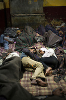 Two young friends lie together in the Fatepuri night shelter for the homeless in Old Delhi.