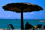 Silhouette of man looking at boats with binnoculars under parasol at Pattaya beach,