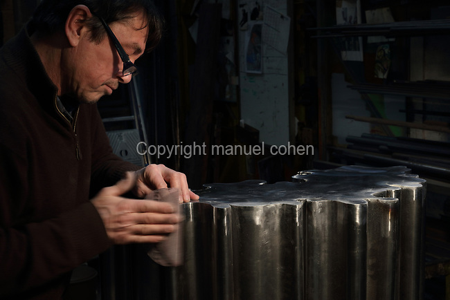 Man working on a steel sculpture with organic form in the Soleil Rouge workshop of Nicolas Desbons, metalworker and artist, photographed in 2017, in Montreuil, a suburb of Paris, France. Desbons works mainly in steel but often in conjunction with other materials such as fibreglass, glass and clay, using both cold metal and forge techniques. He produces both figurative and abstract sculptures as well as furniture and lighting. Picture by Manuel Cohen