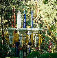 A group of painted concrete pillars with Edward James' artistic embellishments creates a colourful splash in the garden