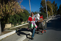Tunis, January 15, 2011.A teenager carries loot stolen from a Monoprix shop in Carthage.