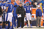 13 October 2012: Kansas head coach Charlie Weis in driving rain during the first quarter. The Oklahoma State University Cowboys played the University of Kansas Jayhawks at Memorial Stadium in Lawrence, Kansas in a 2012 NCAA Division I Football game.