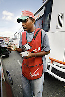 Dominican Republic. La Altagracia Province. Higüey. A young man sells in the street pre-paid phone cards for the mobile Verizon telephone company. He stands in the middle of the traffic jam near a public bus of the town. © 2006 Didier Ruef