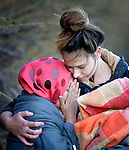 A volunteer embraces a sobbing refugee woman who just landed on a beach near Molyvos, on the Greek island of Lesbos, on October 31, 2015, after crossing the Aegean Sea from Turkey. Local and international volunteers welcomed the arriving refugees with food and medical care and dry clothes before the newcomers proceeded on their way toward western Europe. Their boat to Greece was provided by Turkish traffickers to whom the refugees paid huge sums.