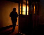 Blurred woman walking towards light in church.