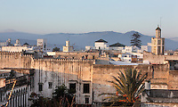 Rooftops of the medina or old town with mountains in the distance and the minaret of the 18th century Zaouiat Sidi ali Benraisoun or Octagonal Mosque on the right, Tetouan, on the slopes of Jbel Dersa in the Rif Mountains of Northern Morocco. Tetouan was of particular importance in the Islamic period from the 8th century, when it served as the main point of contact between Morocco and Andalusia. After the Reconquest, the town was rebuilt by Andalusian refugees who had been expelled by the Spanish. The medina of Tetouan dates to the 16th century and was declared a UNESCO World Heritage Site in 1997. Picture by Manuel Cohen