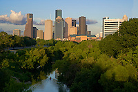 Stock photo of a kayaker paddling down Buffalo Bayou toward Houston skyline
