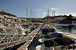 Hotels overlooking harbour, boats and floating pontoon at Puerto Rico, Gran Canaria, Canary Islands, Spain.