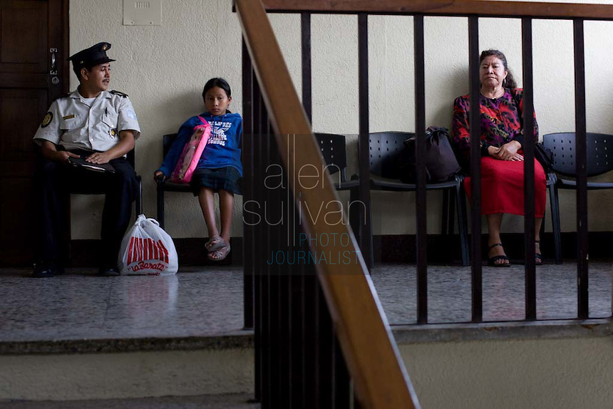 A young Mayan girl sits with a police officer in the children's court in Guatemala City. The officer said he found her alone, begging for money in the central park. The girl said her closest relatives are her parents in Quiche, hundreds of miles from the capitol.