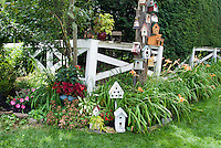 Adorable tower of bird houses full of whimsy, painted and different to attract birds to the garden