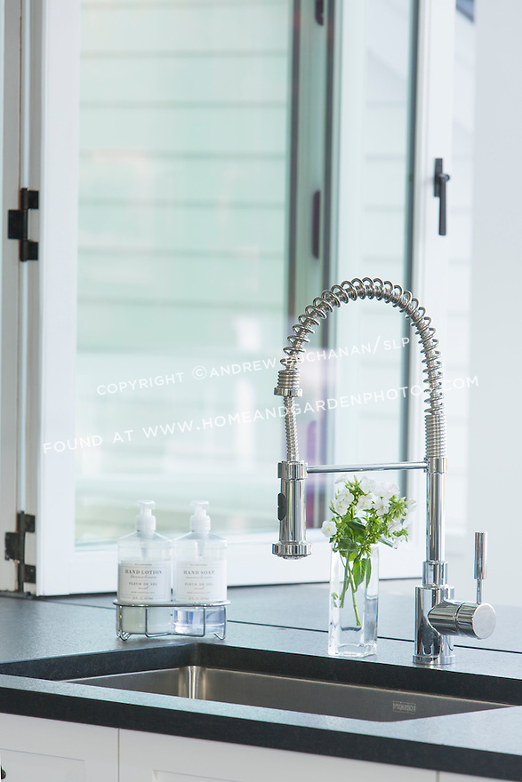 A modern faucet contrasts with the traditional white cabinetry and stone countertops. This image is available through an alternate architectural stock image agency, Collinstock located here: http://www.collinstock.com