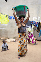 Senegal. Dakar. Marie is a sex worker. She carries on her head a bucket full of water. Marie has been approched by ENDA Sante within the programme framework of the Global Fund and ANCS (Alliance Nationale contre le Sida). ENDA Sante is in charge of the component Advocacy prevention and care of vulnerable groups, such as sex workers, in a fight towards HIV Aids. The Global fund supports ANCS and ENDA Sante with a financial grant. 08.12.09 © 2009 Didier Ruef