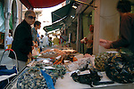 Customers buying from fish vendors at the Rialto market, Venice, Italy. May 2007.