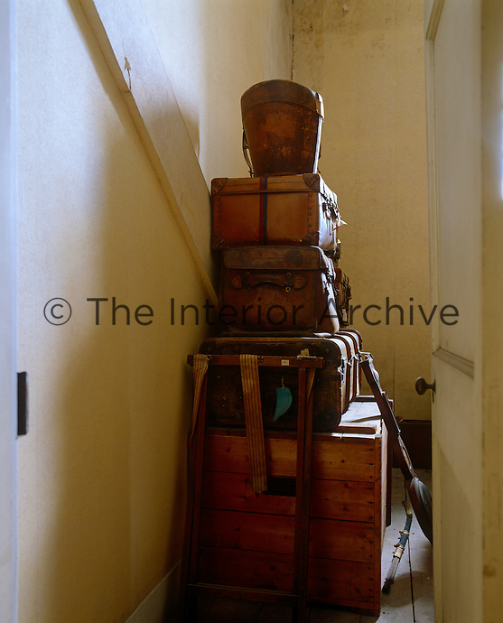 A glimpse into an attic room reveals a stack of vintage trunks, leather suitcases and a hat box