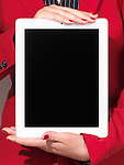 Closeup of a woman in red business suit holding an iPad with blank screen in her hands
