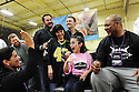 Tani Austin, co-founder of the Starkey Hearing Foundation, high-fives nine-year-old Maci Rowen who heard for the first time, while sitting next to former Saints player Deuce McAllister after getting fitted with a hearing aid at The Citi Garth Brooks Super Pro Camp on Friday, Feb. 1, 2013 in New Orleans. (Photo by Cheryl Gerber/Invision for Starkey Hearing Foundation/AP Images)