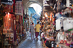 Shoppers stroll the tunnels of the Medina (old city) in Tunis, Tunisia.  The Tunis Medina is a UNESCO World Heritage Site.