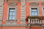 A pink building with details around the windows and balconies in Lugano, Switzerland