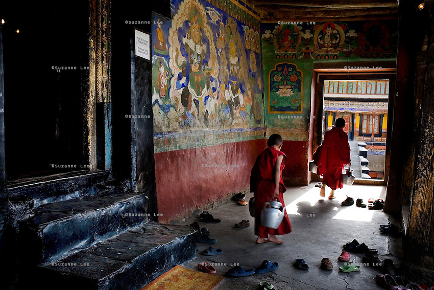 Young monks refill kettles of tea while special prayers commence at Thiksay Monastery, Leh, Ladakh, Jammu & Kashmir, India on the morning of 1st June 2009. Thiksay, founded in the 15th century, sits on a hill 19 km southeast of Leh town, and houses approximately 100 monks.  Photo by Suzanne Lee