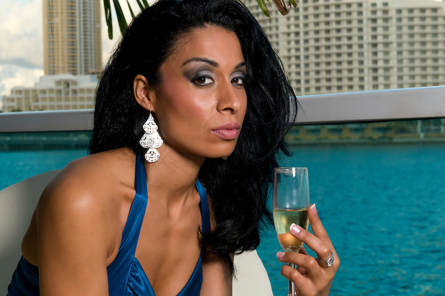 Portrait of hispanic woman drinking champagne in an outodoor terrace