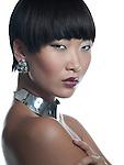 Beautiful asian brunette model in silver necklace & earrings close-up