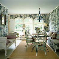 Garden chairs surround a glass-topped table in this dining room whose walls have been covered in a fabric of life-size lilac blossoms