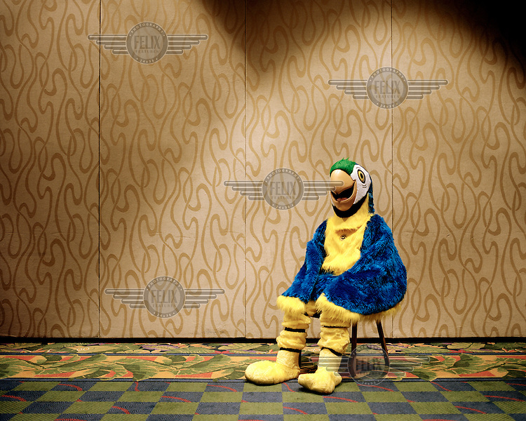 'Zonie', a parrot costume mascot, rests on a chair during the 2013 Panama Canal Society Reunion at the Marriott Hotel in Orlando, Florida.